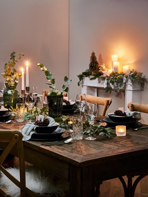Drewniany, prostokątny stół udekorowany w stylu rustykalnym z dużą ilością roślin