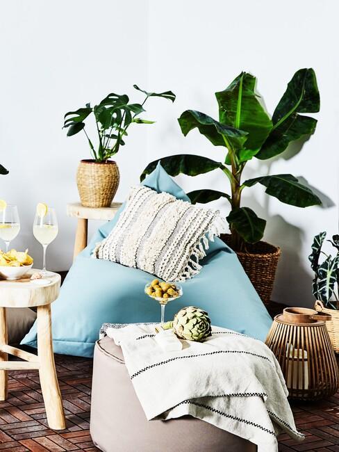 Kącik w trendzie biofilii z roślianmi, poduszkami, na któych można usiąść oraz drewnianym stoliczkiem