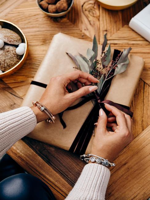 Prezent opakowany w brązowy papier z czarną wstążką oraz suszonymi roślinami