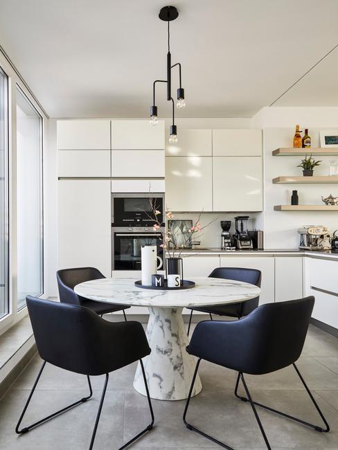 Biała kuchnia połączona z jadalnią z białymi meblami kuchennymi, okrągłym sotłęm i granatowymi krzesłami