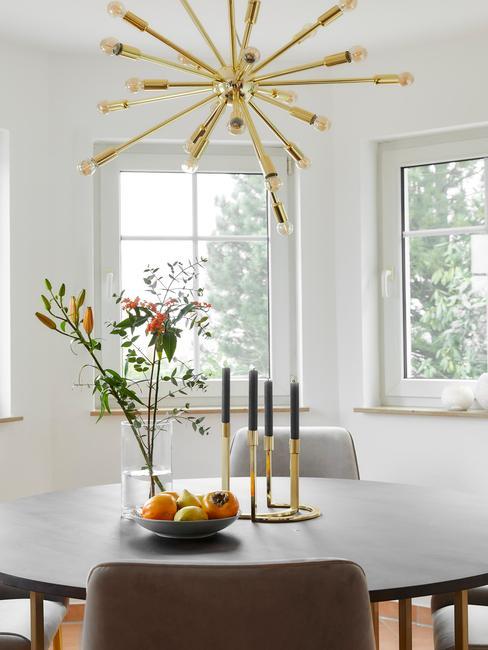 Zbliżenie na drewniany, okrągły stół w jadalni ze złotym świecznikiem wazonem kwiatów oraz miską owoców