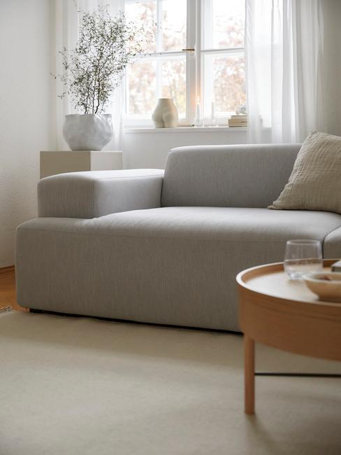 Szara sofa z drewnianym stolikiem kawowym oraz stoliczkiem pomocniczym z wazonem