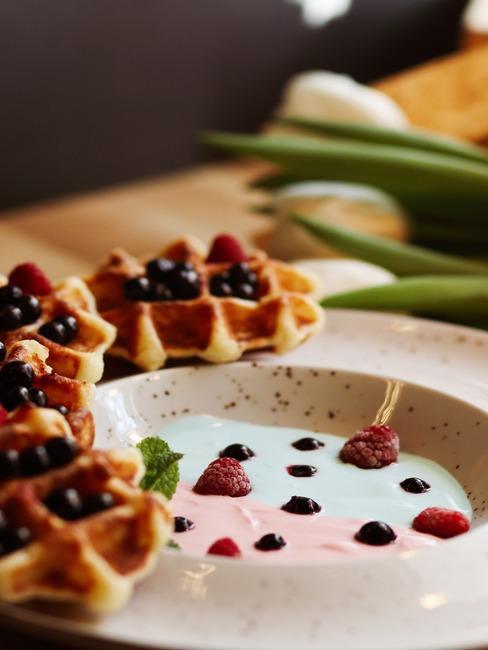 Gofry z Liege ułożona na okrągłym talerzu z jogurtem i owocami
