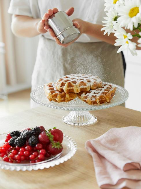 Gofry z Liege na białej paterze na drewnianym blacie oraz biały talerz z owocami