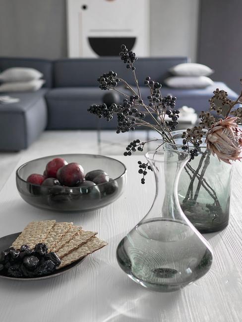 Stół a na nim misa ze śliwkami i ciasteczkami. W wazonie świeże kwiaty