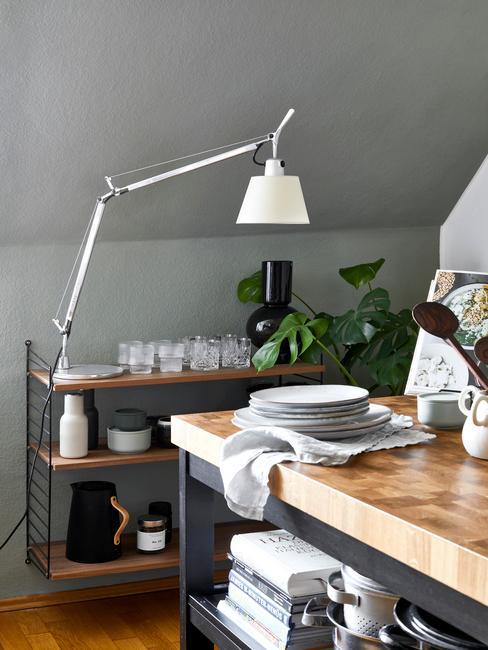 Kuchnia na poddaszu mieszaknia z drewnianym blatem, białą lampą oraz stolikiem barowym