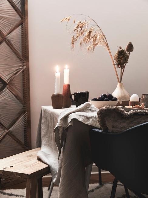 Stół jadalny w ciemnych barwach z wazonem z suszonymi kwiatami