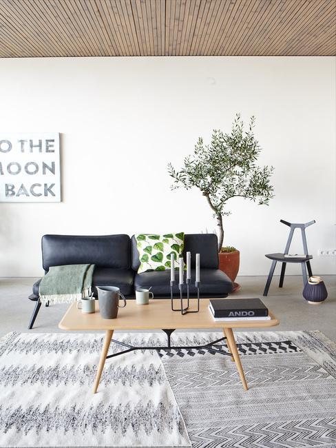 Salon w stylu skandynawskim w czarną kanapą, rośliną, drewnianym stolikiem oraz dywanem