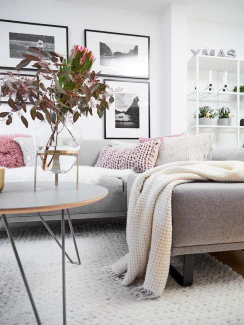 Szara sofa z jasnymi dodatkami. Na ścianie czarno-białe fotografie