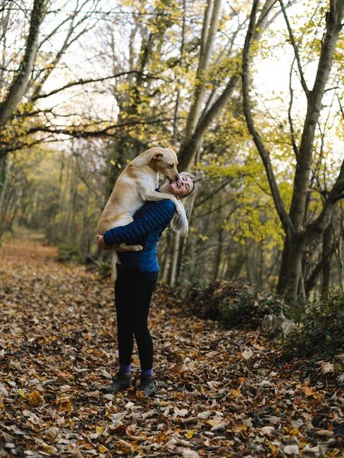 Dziewczyna z psem stojąca w lesie