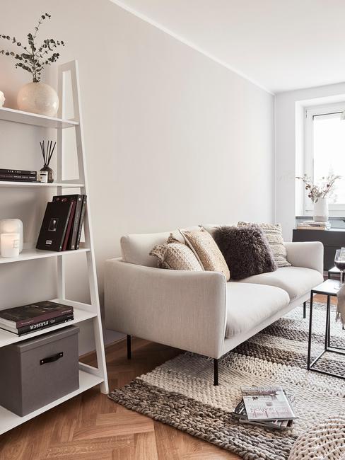 Salon urządzony w duńskim stylu z jasną sogą i białym regałem