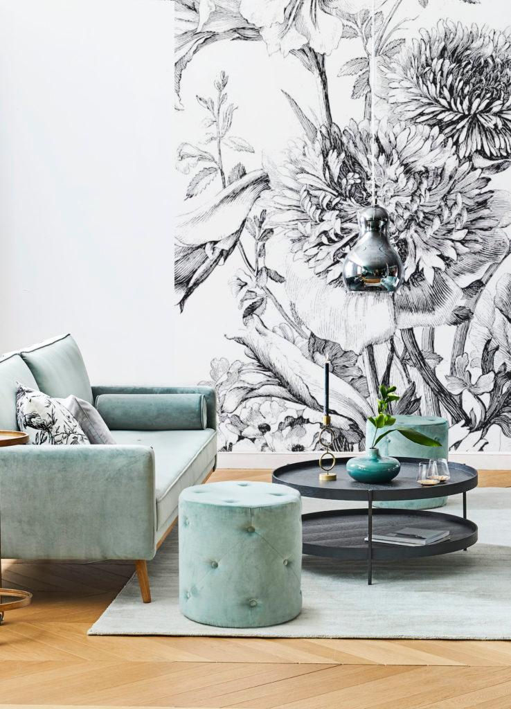 Szałwiowo-zielona sofa, puf i dywan oraz czarny stolik z zielonymi wazonami