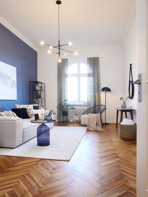 Bialy salon z niebieską ścianą, sofą oraz drewnianą podłogą