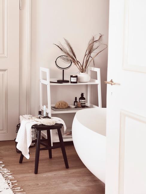 Biała łazienka z wanną, drewnianym stołkiem oraz białą półką z dekoracjami