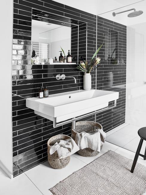 Czarno-biała łazienka w stylu skandynawkim z rattanowymi koszami i stołkiem