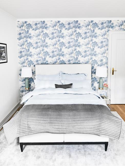 Sypialnia z biało-niebieską tapetą oraz podwójnym łóżkiem z szarą narzutą