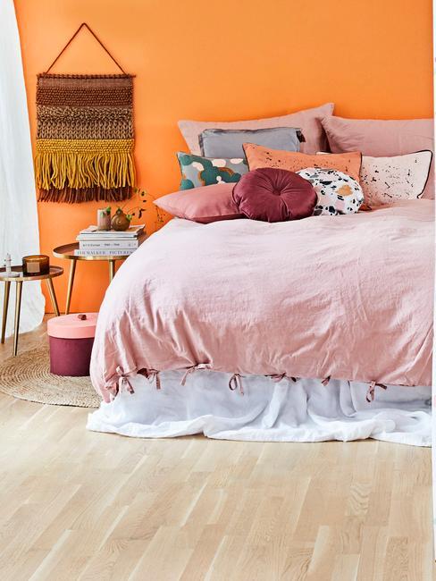 Pomarańczowa sypialnia z łóżkiem o różwowej pościeli