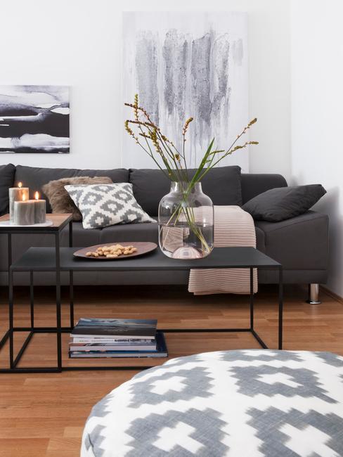 Salon w bloku z jasną ścianą, ciemnoszara sofą, białym pufem oraz czarnym stolikiem kawowym