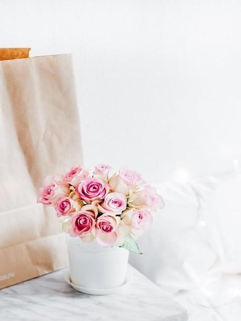 Torba prezentowa i doniczka z kwiatami na stoliku