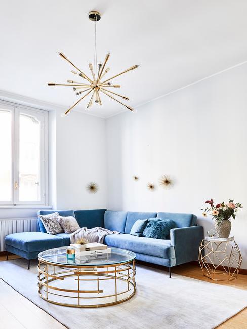 Salon w stylu glam z niebieską, aksamitną sofą i złotymi dodatkami