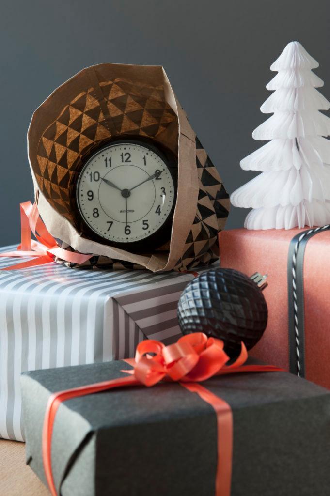Zegar w torebce prezentowej, leżący na pudełku oraz zapakowany prezent