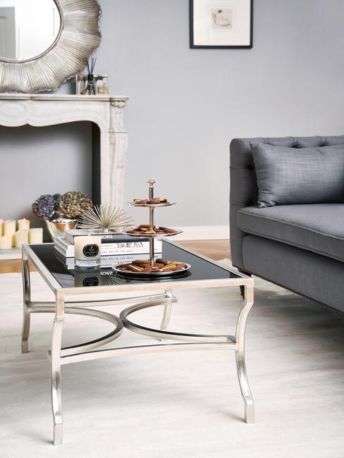Fragment szarego salonu z czarn kanap, stolikiem kawowym