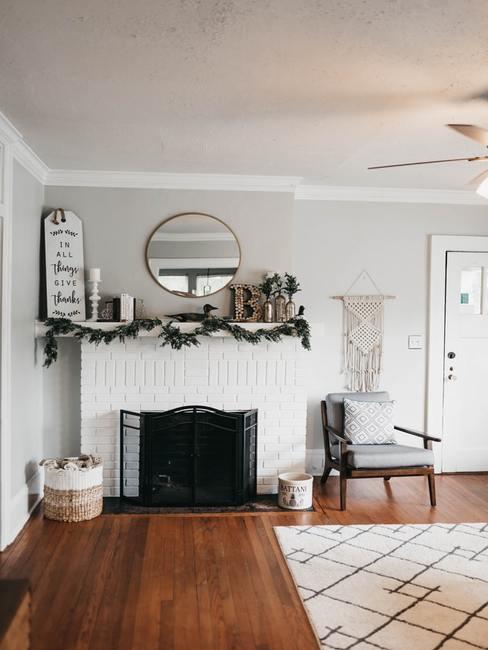 Biay salon z fotelem i dywanem, kominkiem i lustrem