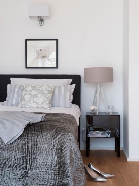 Sypialnia z łożkiem o czarnym obiciu, czarnym stoliku nocnym oraz lampa