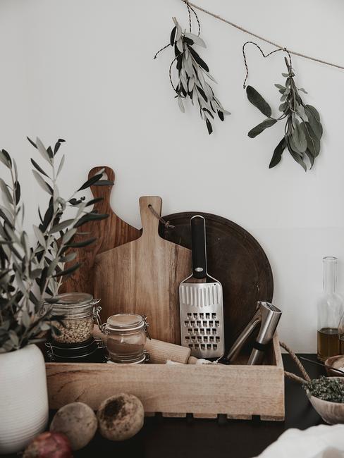 Biała kuchnia z drewnianym blatem oraz drewnianymi akcesoriami