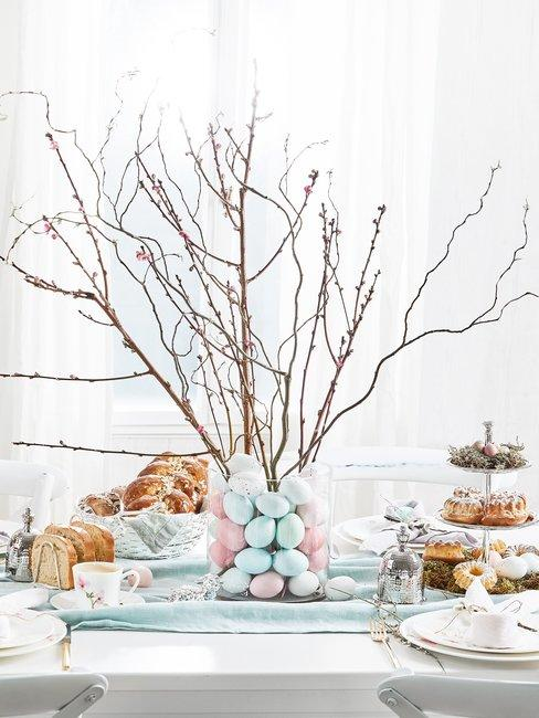 Ozdoba wielkanocna wykonana z gałęzi oraz jajek w wazonie stojąca na zastawionym stole