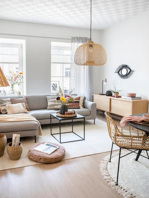 Salon z szarą, narożną kanapą, komodą, stolikiem kawowym oraz stołem