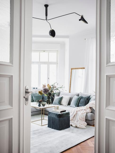 Fragment salonu niebieską kanapą, poduszkami, pufem oraz stolikiem kawowym