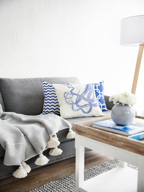 Szara kanapa z kocem i niebieskimi poduszkami oraz drewniany stolik
