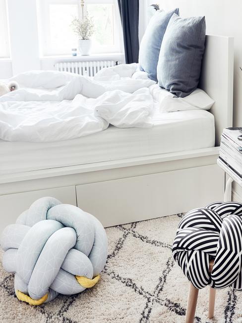 Białe łóżko z szufladami w błękitno-białej sypialni