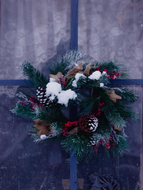 Zimowy wianek na drzwi z szyszek, jodły i ileksu przypruszony śniegiem