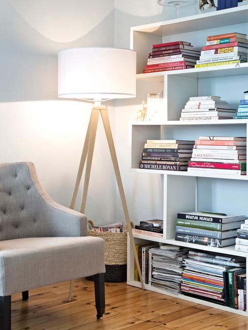 Kącik do czytalnia w salonie z szarym fotelem, półtką oraz lampą