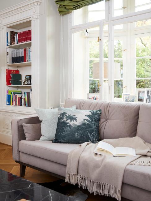 Salon z szarą kanapą, poduszkami oraz regałem na książki