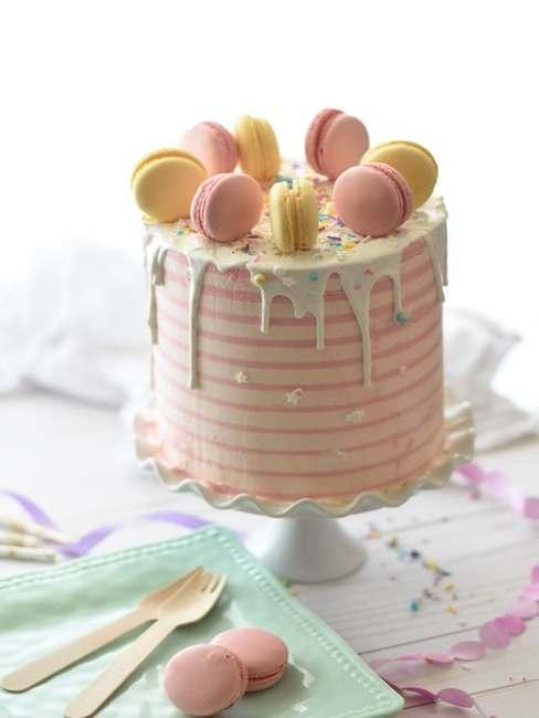 Wysoki, pastelowy tort udekorowany makaronikami ustawiony na paterze