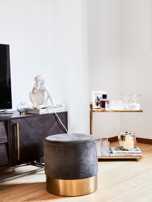Fragment białego salonu ze złotym wózkiem barowym oraz antracytowym pufem