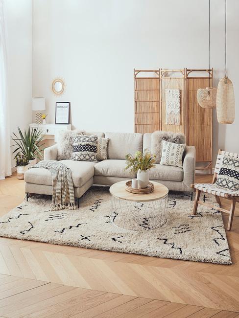 Salon w stylu boho, z beżową sofą, okrągłym stoliczkiem, parawanem, dywanem oraz rośliną w doniczce