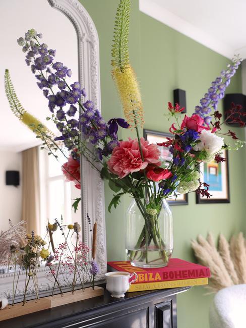 Zbliżenie na bukiet kwiatów w szklanym wazonie ustawiony na książkach na kominku z trawą pampasową w tle
