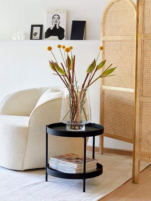 Salon w stylu boho z parawanem orgodowym, czarnym stolikiem kawowym, białym fotelem oraz wiszacą półką