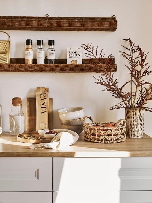 Białą kuchnia z drewnianym blatem, na któym znajdują się akcesoria kuchenne oraz półka ścienna z przyprawami