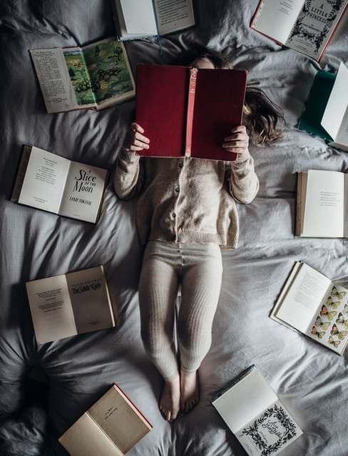 Dziecko czytające na łóżku wokół książek