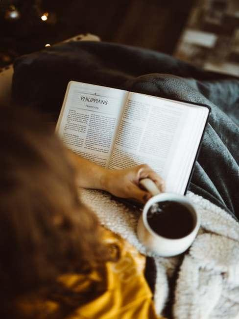 Osoba czytająca książkę pod kocem z kubkiem herbaty