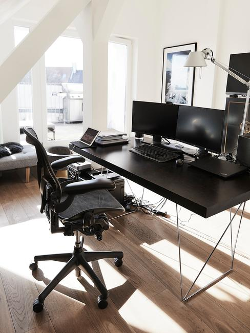 Minimalistyczne domowe biuro z czarnym biurkiem oraz fotelem w mieszkaniu na poddaszu