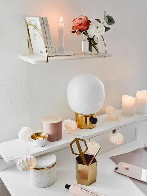Białe biurko z dekoracjami w postaci lampki, świec i wiszącej nad nim półki z wazonem i książką