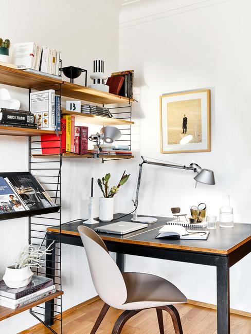Kącik w salonie przeznaczony na domowe biuro, w któym znaduje się niurko, krzesło, lampka oraz regał na dokumenty
