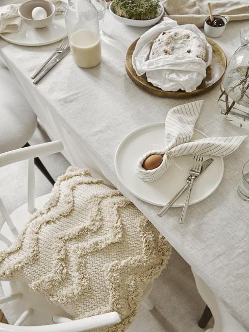 Stół nakryty lnianym obrusem, białą zastawą i pisankami