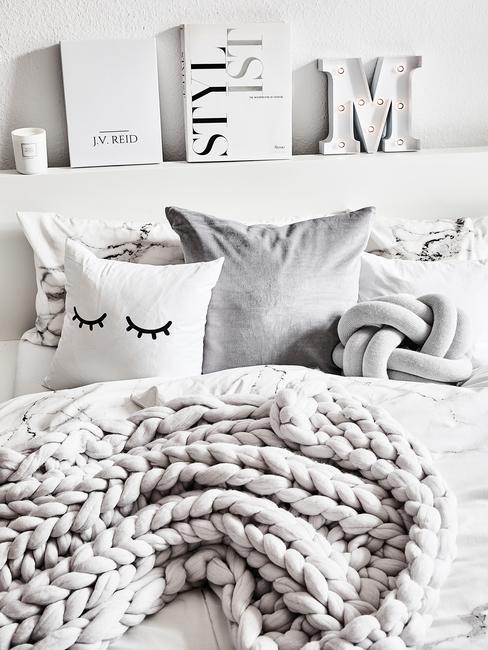 Łóżko  z grubym, pledowym kocem, poduszkami, nad którym znaduje się półka z dekoracjami